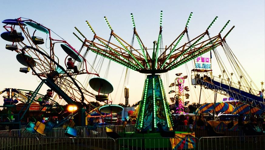 Midway Carnival rides at dusk lit up for the Hunt County Fair